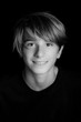 young blonde smiling guy portrait on black background - black and white photo