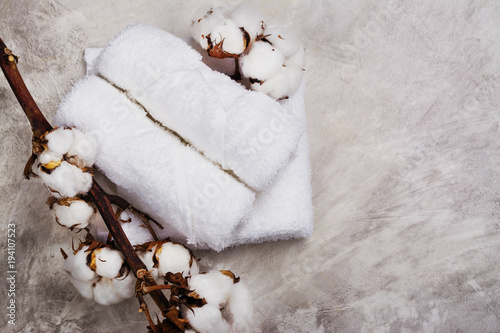 Stack of cotton towels, branch with cotton flowers, soap and tea candle on grey stone background