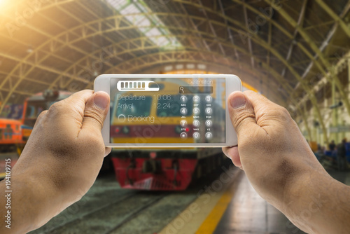 Hands holding a phone with virtual reality technology in a train station to book a train destination