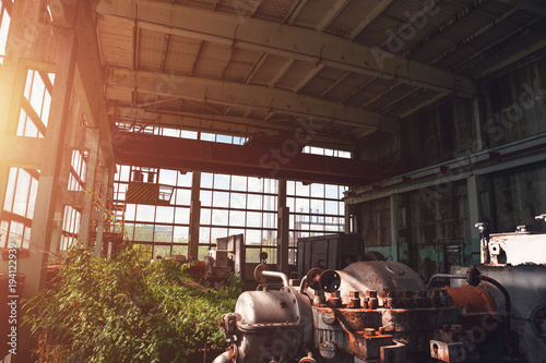 Papiers peints Les vieux bâtiments abandonnés Abandoned industrial creepy warehouse inside old dark grunge factory building with steel rusty equipment at sun light