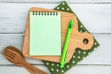 Notepad on chopping board with wooden fork and spoon on white table , recipes food or diet plan for healthy habits shot note background concept - 194130310