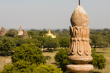 Architectural detail of a pagoda in the foreground and the pagoda field of Bagan out of focus in background, Myanmar
