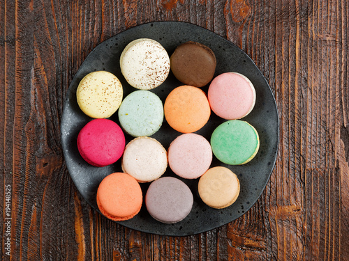 Aluminium Macarons Brightly colored macaroons on a hand-made plate, set on a rustic brown wooden board