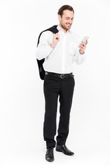 Full-length portrait of pleased office worker smiling and using cellphone while holding black jacket in hand, isolated over white background © Drobot Dean