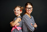Portrait of pretty girls in optical glasses. Smiling family wearing spectacles over black background.