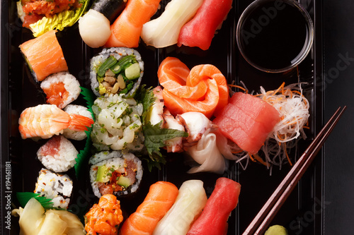Fotobehang Sushi bar fresh traditional Japanese sushi with scallops, tuna, shrimp, mix rolls, octopus sashimi, salmon, tuna, top view. food delivery. A large set of sushi, rolls, sashimi in the package.