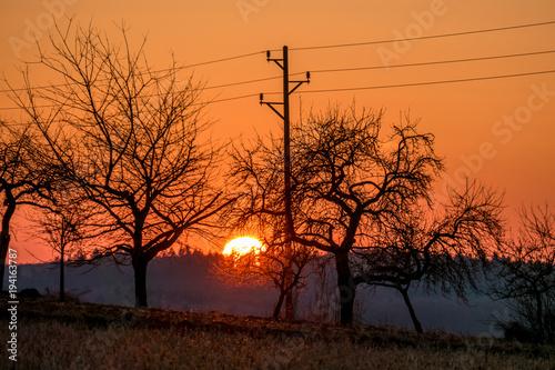 Staande foto Oranje eclat Strommast bei Sonnenuntergang