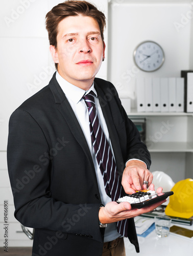 Man worker calculating in the office - 194166901