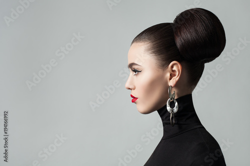 Fotobehang Kapsalon Fashion Portrait of Elegant Young Woman with Hair Bun Hairstyle and Eyeliner Make up. Cute Female Model wearing Black Roll Neck Jersey, Profile Portrait.