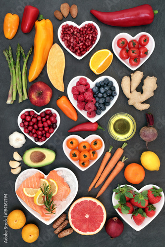 Food to maintain a healthy heart concept with salmon, vegetables, fruit, spice, nuts on slate background. Super foods high in antioxidants, vitamins, minerals, omega 3 fatty acids and anthocyanins.