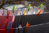 Closeup of laundry, on a wire with plastic clips - 194170363
