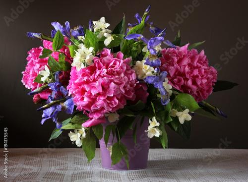 Fotobehang Iris Peonies, irises and Jasmine in a bouquet. Garden flowers in a vase.