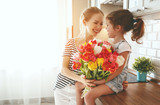 Fototapeta happy mother's day! child daughter gives mother a bouquet of flowers to tulips.