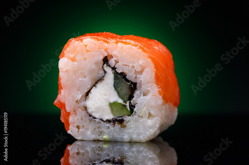 Tuinposter Sushi bar One roll with red fish and cucumber on a black background. Japanese restaurant menu, close-up