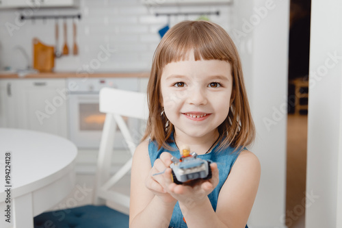 Little baby girl shows her new toy car on white background. Smiling and looking frame.