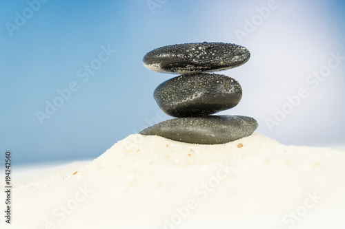 Plexiglas Zen Stenen Three black stones in the sand, blue sky background