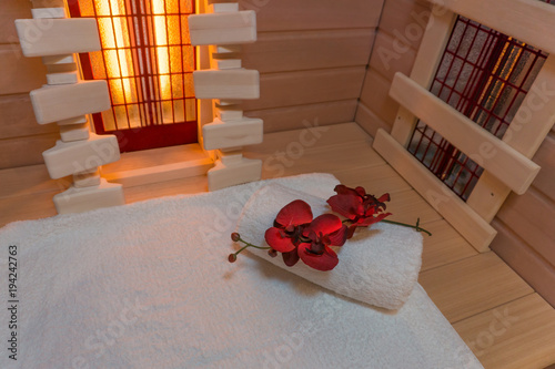 Leinwanddruck Bild Private infrared cabin with a white towel and a beautiful flower