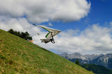 Pilot runs with a hang glider on a green grassy slope high in the mountains with blue sky and clouds above - 194245535