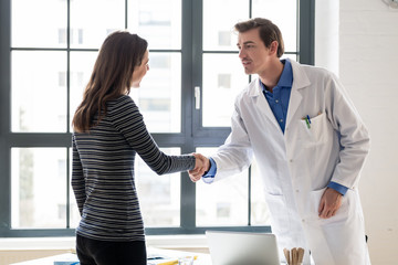 Young dedicated reliable physician and female patient shaking hands before consultation in the office of a modern medical center