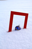 Red  frame and Christmas bauble on fresh snow
