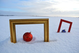 Two  frame and Christmas baubles on snow on field