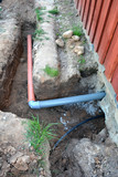 Trench near house with water and sewerage pipes