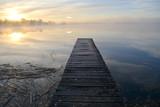 Old wooden lake bridge and autumn morning mist