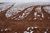Autumn plowed  field with tractor traces and first snow