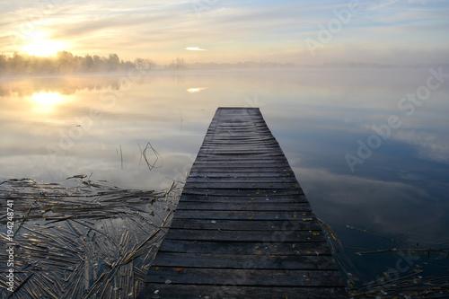 Tuinposter Herfst Old wooden lake bridge and autumn morning mist