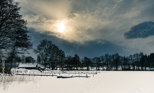 Aluminium Pier Lake with jetty and boats in winter in the snow, beautiful sky and clouds in the back light