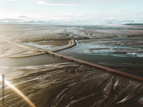 Foto op Canvas Grijze traf. Aerial view of Iceland winter texture, frozen glacier river, bridge, road, delta of river, volcano, black sand, mountains, abstract landscape
