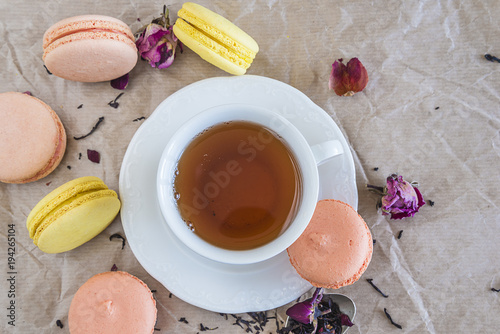 Aluminium Macarons Tea time with french macaroons/white cup of tea, french macaroons and rose petals on crumpled paper with copy space