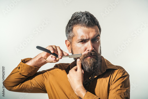 Professional barber with thick beard and mustache, holding straight razor. Hairdresser demonstrating sharp blade of barbershop accessory. Young bearded macho shaving with razor blade.