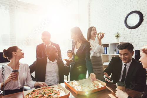 Papiers peints Pizzeria The office staff eat pizza and drink coffee in the business office.