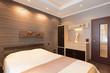bedroom in brown tones with designer details on wall and  door
