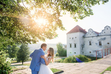 Groom holds bride tender posing with her before an old castle in a sunny summer day