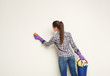 Young woman washing wall with sponge
