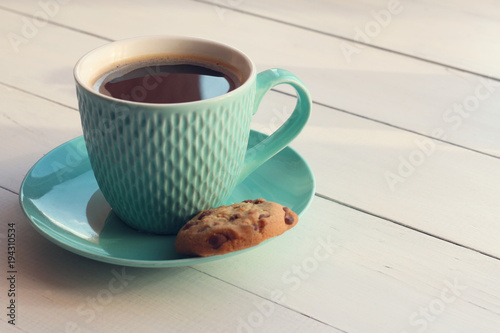 Coffee in a turquoise mug and cookies with chocolate on a white wooden table