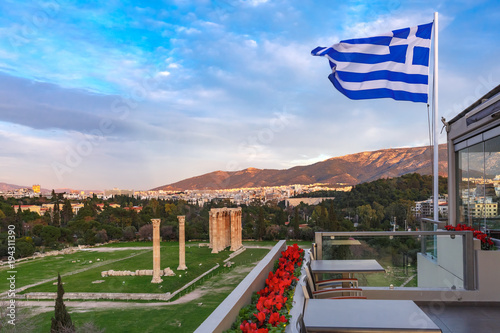 In de dag Athene Large waving Greek flag against the blue sky. Ruins and a columns of the Temple of Olympian Zeus in the background, Athens, Greece