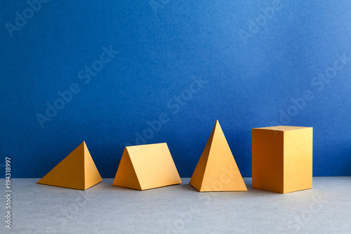 Abstract geometric figures. Three-dimensional pyramid tetrahedron cube rectangular objects on blue gray background. Yellow color Platonic solids still life background