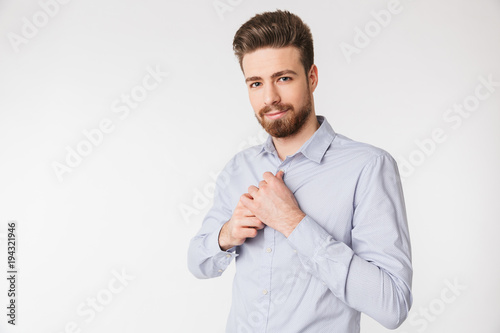 Portrait of a smiling young man buttoning