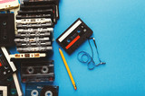 Vintage cassettes and pencil to rewind tape on blue background