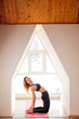 young attractive woman in back reversed yoga pose, side view, dressed in black