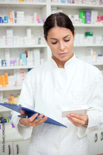 Fotobehang Apotheek Beautiful young pharmacist holding clipboard and a box of medications