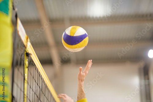 Fototapeta The volleyball player's hand in the covered gym fights the ball in front of the net,
