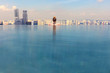 Leinwanddruck Bild - Woman Looking At Cityscape While Relaxing In Infinity Pool