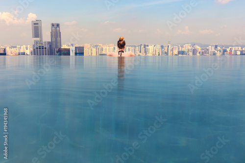 Leinwanddruck Bild Woman Looking At Cityscape While Relaxing In Infinity Pool