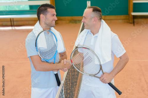 Fotobehang Tennis Men shaking hands over tennis court net