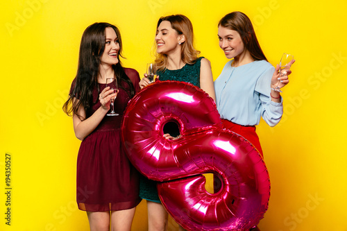 Happy Women's Day. Smiling attractive girls drinking a champagne, celebrating international holiday, March 8, holding big air balloon in form of number eight.