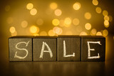 Sale word chalk written on black cubes on blurred bokeh background